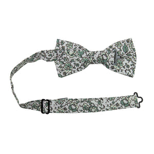 Hidden Garden Pre-Tied Bow Tie with adjustable neck strap. White background with sage green flowers and leaves with black vines.