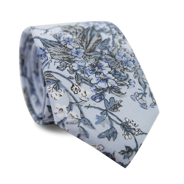 Indie Skye Skinny Tie. Dusty blue background with white, blue, black and gray floral leaf pattern.
