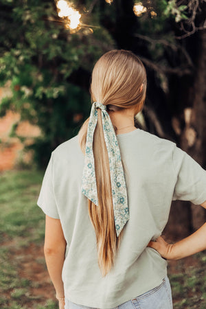 Island Breeze hair tie worn tied around a ponytail in a single knot. Model has brown hair.