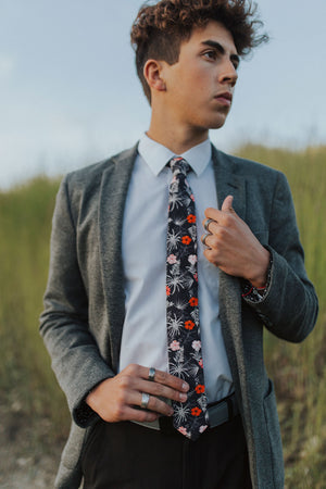 Islander tie worn with a white shirt, gray textured suit jacket and black pants.