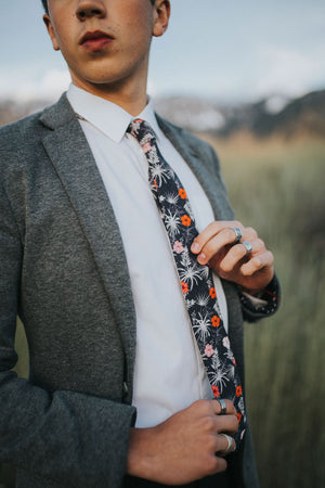 Islander tie worn with a white shirt and gray textured suit jacket.