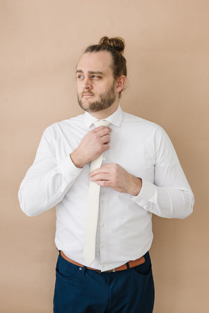 Ivory tie worn with a white shirt, brown belt and navy blue pants.
