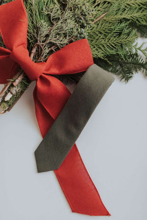 Jungle tie laying on some pine leaves next to a big red bow.