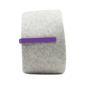 Solid lavender metal tie bar clipped onto a gray textured wool tie that is rolled up.