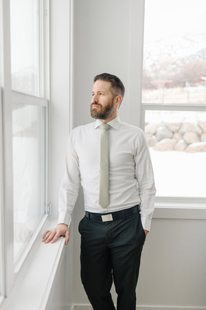 Light Sage tie worn with a white shirt, black belt and black pants.