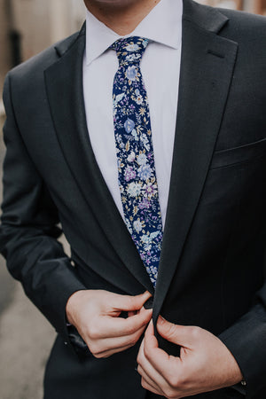 Lilac tie worn with a white shirt and dark gray suit.