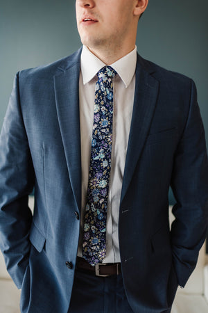 Lilac tie worn with a white shirt and blue suit.