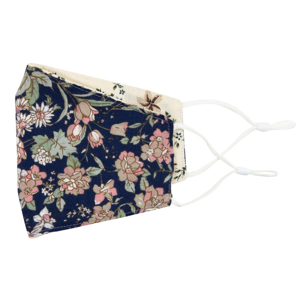 Lotus and Sugar Blossom Reversible Face Mask. Outside is navy background with white and blush pink flowers and sage green stems and leaves. Inside is cream background with medium size mauve flowers, small dusty blue flowers, and sage green leaves. White adjustable straps to loop over ears.