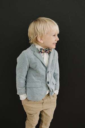 Mardi pre-tied bow tie worn by a young boy in a white shirt, gray blazer and tan pants.