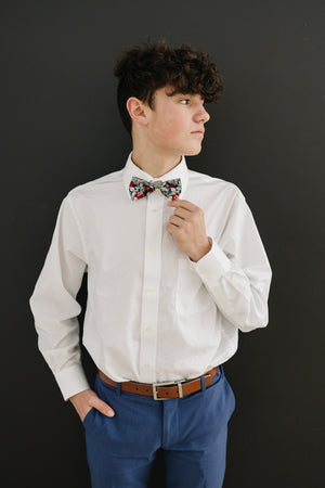Mardi pre-tied bow tie worn with a white long sleeve shirt, brown belt and blue pants.