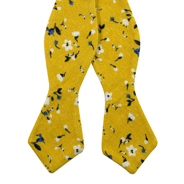 Marigold Self Tie Bow Tie. Yellow background with small white, black and blue flowers.