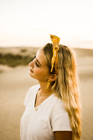 Marigold hair tie worn as a top knot tied around the model's head. Model has blonde hair.