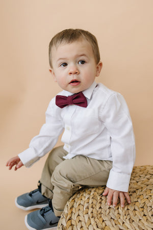 Merlot pre-tied bow tie worn by a young boy in a white shirt and tan pants.