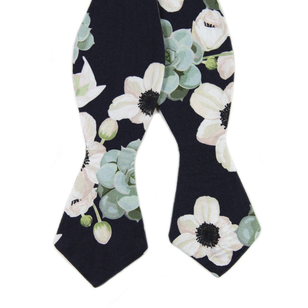 Mesa Self Tie Bow Tie. Navy background with big white flowers and sage green succulents.
