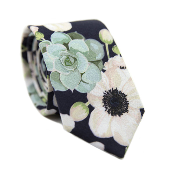 Mesa Skinny Tie. Navy background with big white flowers and sage green succulents.