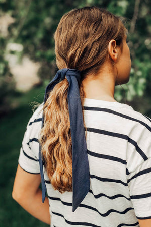Navy hair tie worn tied in a single knot around a ponytail. Model has brown hair.