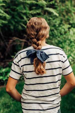 Navy hair tie worn tied in a bow around the end of a braided ponytail. Model has brown hair.