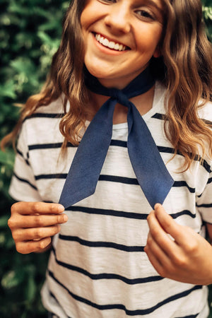 Navy hair tie worn tied around the neck in a single knot. Model has brown hair.
