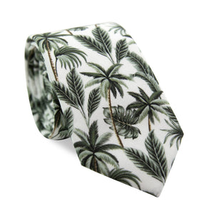 Oasis Skinny Tie. White Background with brown and green palm trees and green palm leaves throughout.