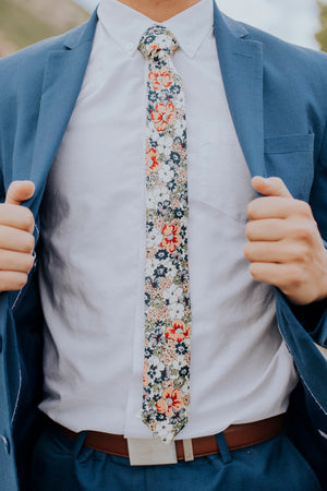 Orange Pansy tie worn with a white shirt, brown belt and royal blue suit.