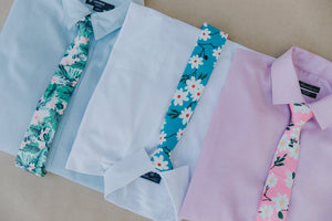 Pacific tie laying on a light blue shirt next to two other shirts with different skinny ties on them.