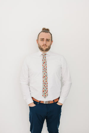 Painted Perennials tie worn with a white shirt, light brown belt and navy blue pants.