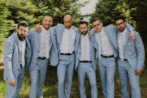 Palm tie worn by 6 groomsmen at a wedding wearing white shirts and light blue suits.