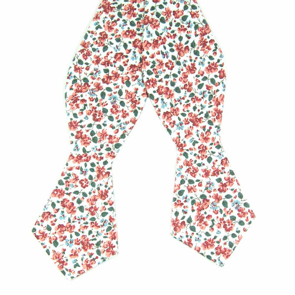 Peach Blossom Self Tie Bow Tie. White background with small red and dusty blue flowers and small green leaves.