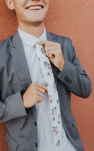 Pixie tie worn with a white shirt and gray suit jacket.