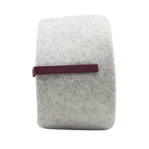 Solid plum metal tie bar clipped onto a gray textured wool tie that is rolled up.