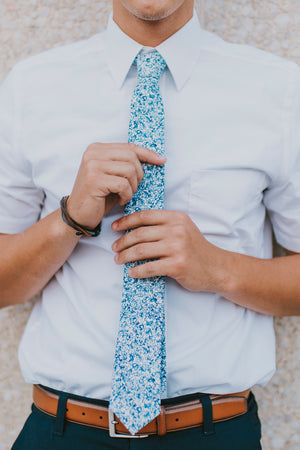 Powder tie worn with a white shirt, brown belt and navy blue pants.