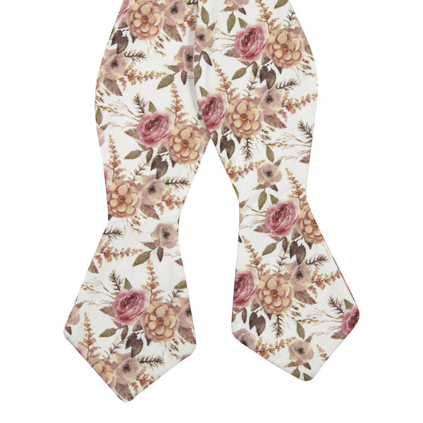 Quicksand Roses Self Tie Bow Tie. White background with mauve, peach and blush pink flowers. Sage green leaves and branches throughout.