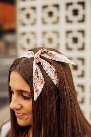 Quicksand Roses hair tie worn as a top knot tied around the model's head. Model has brown hair.