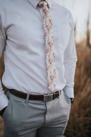 Quicksand Roses tie worn with a white shirt, brown belt and gray pants.