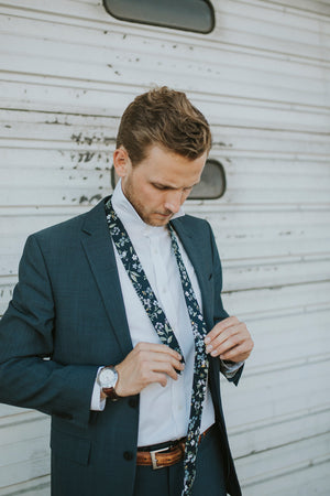 Rio tie worn with a white shirt, brown belt and gray suit.