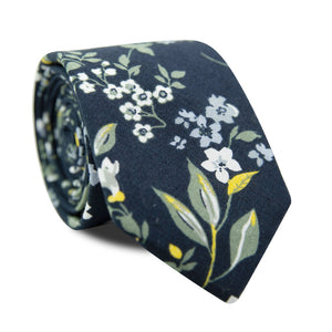 Rio Skinny Tie. Navy blue background with white and light blue flowers, green and yellow leaves and stems.