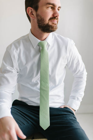 Seafoam tie worn with a white shirt and navy pants.