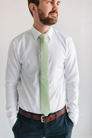 Seafoam tie worn with a white shirt, brown belt and navy pants.