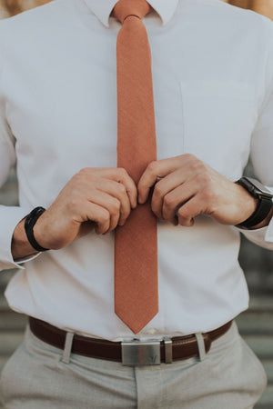 Sedona tie worn with a white shirt, brown belt and light gray pants.