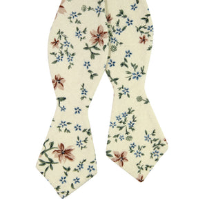 Sugar Blossom Self Tie Bow Tie. Cream background with medium size mauve flowers, small dusty blue flowers, and sage green leaves.