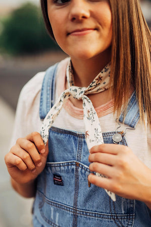 Sugar Blossom hair tie worn tied around the neck in a single knot. Model has brown hair and is wearing denim overalls.