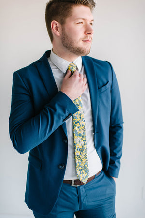Sunburst tie worn with a textured white shirt, brown belt and royal blue suit.