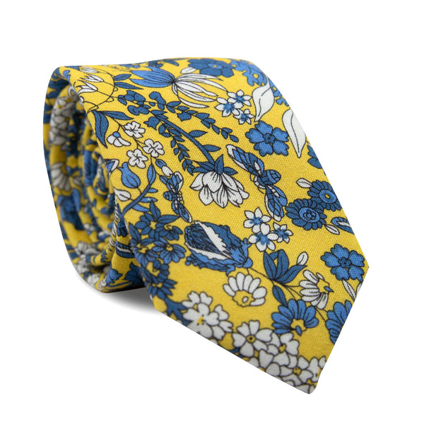 Sunburst Skinny Tie. Yellow background with various types of white and royal blue flowers and leaves.