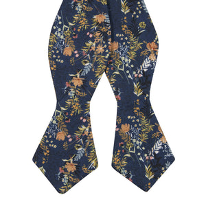 Tiger Lily Self Tie Bow Tie. Dark navy blue background with peach flowers and dusty blue, yellow, green and black leaves.