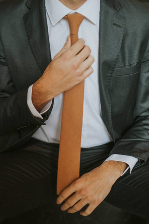 Timber tie worn with a white shirt and dark gray suit.