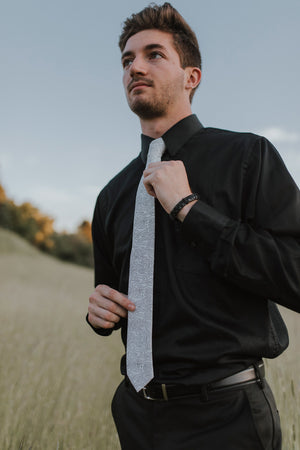 Topographic tie worn with a black shirt, black belt and black pants.