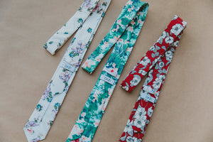 Torch tie laying on a flat surface next to two other floral ties.