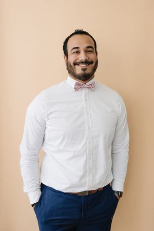 Ventura pre-tied bow tie worn with a white long sleeve shirt and blue pants.