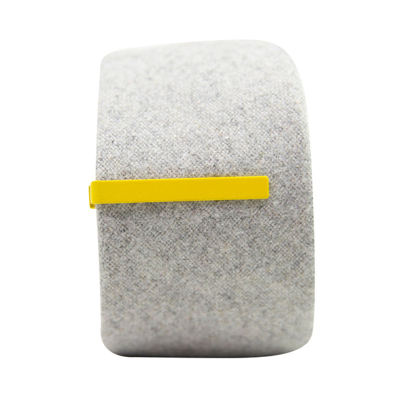 Solid yellow metal tie bar clipped onto a gray textured wool tie that is rolled up.