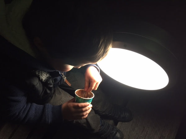 Little boy eating ice-cream with a spoon at night by a floodlight